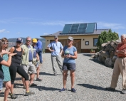 "Solar Ambassador Elaine Brett (middle with cap) opens up her house to a ""Solar Home Tour"" as part of a Solarize educational event. The Brett's 3.36 kW grid-tied PV system meets all their electrical needs. Being grid-tied allows the Bretts to take advantage of DMEA's generous net-metering policy, which credits customers for the excess energy their systems produce. Picture shows the solar hot water system on their garage. The solar photovoltaic system is roof mounted on the adjoining house."