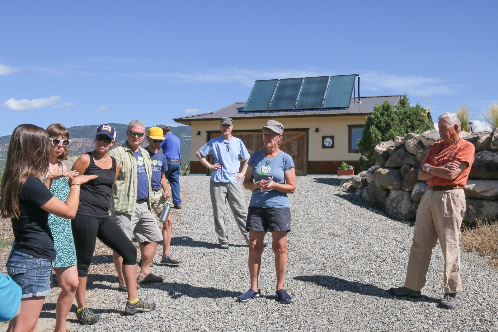 """Solar Ambassador Elaine Brett (middle with cap) opens up her house to a """"Solar Home Tour"""" as part of a Solarize educational event. The Brett's 3.36 kW grid-tied PV system meets all their electrical needs. Being grid-tied allows the Bretts to take advantage of DMEA's generous net-metering policy, which credits customers for the excess energy their systems produce. Picture shows the solar hot water system on their garage. The solar photovoltaic system is roof mounted on the adjoining house."""